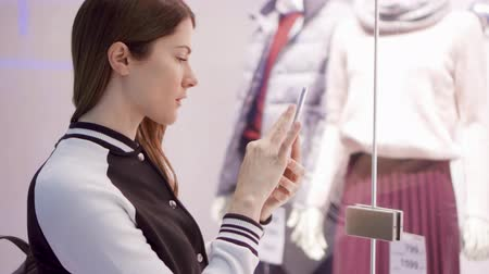qr : Beautiful attractive young woman near window shop with mannequins. Reading QR-codes by smartphone, checking prices online. Shopping at the mall, sales time Stock Footage