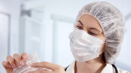 ampulka : Professional female doctor in mask, cap and gloves standing in hospital room holding ampoules with new drug treatment. Woman physician at work. Laboratory employee making scientific research Dostupné videozáznamy