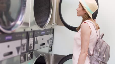 utilidade : Young woman in hat at laundry machines room. Reading how to use public laundromat to wash clothes.