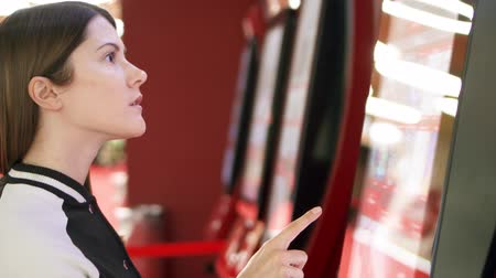 ticket machine : Teenager choosing movie and buying ticket from vending machine at movie theater at mall. Young woman making gestures by touching screen