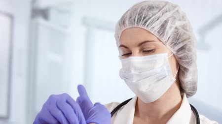 szakértő : Confident professional female doctor in mask and cap in hospital room putting blue medical gloves on. Woman physician at work. Health care concept. Laboratory employee