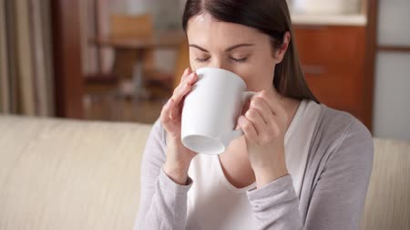 меланхолия : Young woman relaxing sitting on couch at home in the morning. Pretty female drinking tasty coffee or tea from white cup in living room Стоковые видеозаписи