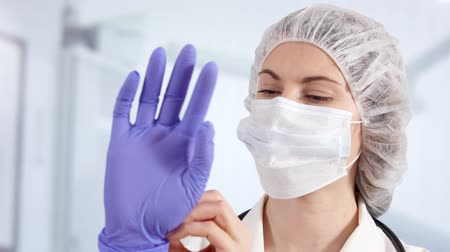 медик : Confident professional female doctor in mask and cap in hospital room putting blue medical gloves on. Woman physician at work. Health care concept. Laboratory employee