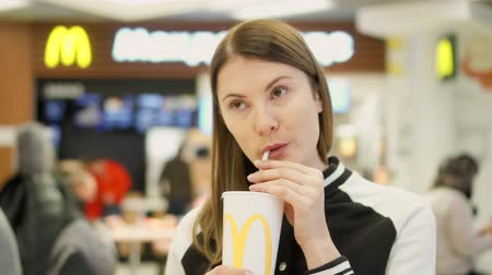 mcdonalds : MOSCOW, RUSSIA - CIRCA November 2017: Thirsty teen girl drinking soda from paper cup at McDonalds fast food restaurant on food court