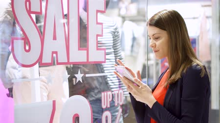 qr : Beautiful attractive young woman near window shop. Sale sign. Reading QR-codes by smartphone, checking prices online. Shopping at the mall, sales time Stock Footage
