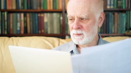 starszy pan : Senior man with laptop computer at home working with paper documents. Remote freelance or office work on retirement, active modern lifestyle of older people. Bookcase bookshelves in the background