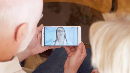 mensageiro : Top view of senior couple at home having medical consultation video chat on mobile with physician. Confident professional female doctor with stethoscope talking with patients via messenger app call Stock Footage
