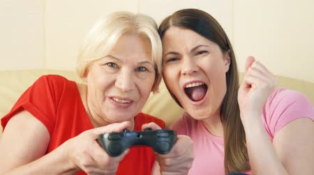 gameplay : Mother and daughter gamers playing video games at home. Addicted senior and teen players with remote controller of game console. Cybersport for active modern elderly people Stock Footage