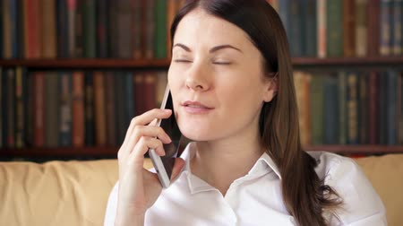 telefonkönyv : Woman at home talking on mobile. Young female professional in white shirt having conversation on smartphone. Recieving good news happy cheerful smiling. Remote freelance work. Home-office concept Stock mozgókép