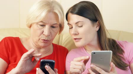 senior lifestyle : Mother and daughter sitting on couch at home. Using smartphones, browsing, reading news. Loneliness in technology era concept. Active modern lifestyle of older people