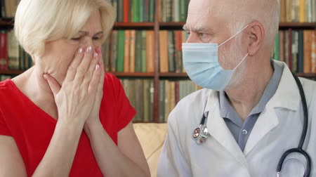 плохо : Male professional doctor in white coat and medical mask at work. Senior man physician talking to sick coughing badly senior female patient at home consulting about treatment and therapy options Стоковые видеозаписи