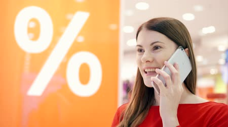 barganha : Beautiful attractive young woman near window shop with mobile phone. Sale percent sign. Female shopper joyfully talking on smartphone, telling friend about big sales. Shopping at the mall, sales time Vídeos