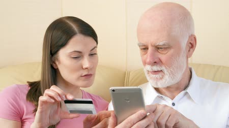 szülő : Father and daughter shopping online with credit card on smartphone at home. Concept of technology use by older people. Active modern life after retirement