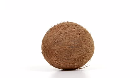 rehydration : One ripe whole brown tropical coconut rotating on white isolated background. Healthy tropical fruit. Loopable seamless coco rotating Stock Footage