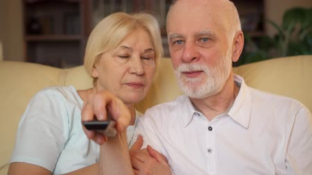 box set : Senior couple relaxing on sofa at home. Happy family enjoying time together watching TV. Pensioners switching channels with remote control Stock Footage