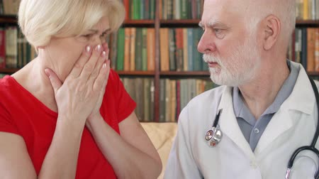 плохо : Male professional doctor in white coat with stethoscope at work. Senior man physician talking to sick coughing badly senior female patient at home consulting about treatment and therapy options
