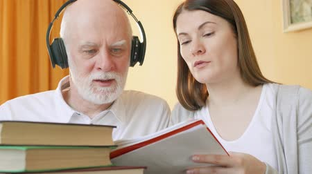 schoolbook : Teacher giving listening lesson to senior student. Tutor explaining foreign language pronunciation to senior man in wireless headphones. Active life after retirement. Education among elderly concept Stock Footage