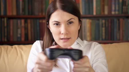 gameplay : Businesswoman gamer in white shirt playing video games at home. Addicted player with remote controller of game console. Cybersport for active modern people. Bookcase bookshelves in the background