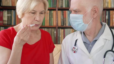 temp : Male professional doctor in white coat and medical mask at work. Senior man physician measuring temperature to sick senior female patient by thermometer at home. Consulting about treatment and therapy
