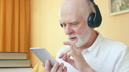 pronunciation : Senior man in wireless headphones using online application for listening skills training. Student learning foreign language on smartphone. Active life after retirement. Education among elderly concept