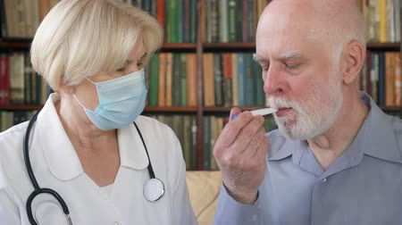 gyógyszerek : Female professional doctor in medical mask at work. Senior woman physician measuring temperature to sick senior male patient by thermometer at home. Consulting about treatment and therapy