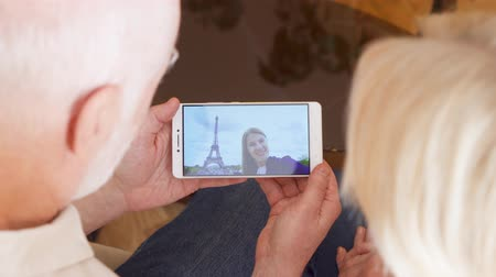 telephone tower : Top view of retired senior couple at home having video chat on mobile with their daughter from Paris, France. Eiffel Tower on background. Student abroad talking to her parents via messenger app call