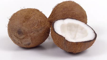 rehydration : Two whole ripe brown tropical coconuts and a half with yummy white pulp on white isolated background. Healthy fresh tropical fruits. Zooming dolly shot