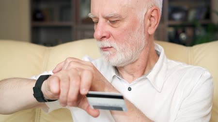 consumerism : Senior man at home using smartwatch. Modern pensioner buying online with credit card on smart watch. Consumerism concept. Technology use by older people. Active modern life after retirement