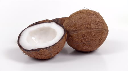 rehydration : One whole ripe brown tropical coconut and two halves with yummy white pulp rotating on white isolated background. Healthy fresh tropical fruits. Loopable seamless cocos rotating Stock Footage