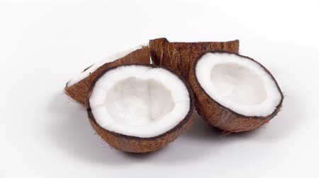 rehydration : Four ripe tropical coconut halves with yummy white pulp rotating on white isolated background. Healthy fresh tropical fruits. Loopable seamless cocos rotating Stock Footage