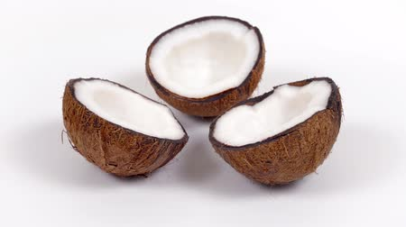 rehydration : Three ripe tropical coconut halves with yummy white pulp rotating on white isolated background. Healthy fresh tropical fruits. Loopable seamless cocos rotating