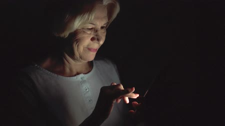 privacy : Lonely elderly senior woman relaxing at home reading news on smartphone. Secretly using mobile at night hiding from people. Dark only face illuminated. Loneliness privacy in technology era concept