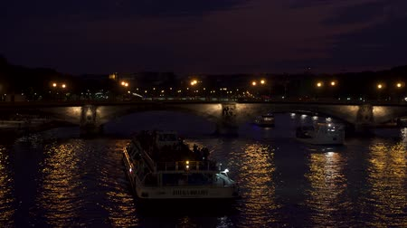 lanterns : PARIS, FRANCE- CIRCA August 2017: Pont des Invalides at night. Tourist boats sailing along Seine river in Paris, France. Bridge lanterns lights reflecting in water Stock Footage