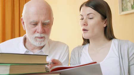 schoolbook : Young teacher giving lesson to senior student. Female tutor explaining foreign language rules to senior man. Active modern life after retirement. Concept of education among elderly people
