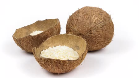 hull : One whole and two shells halves of tropical coconut with dried white coconut flakes rotating on white isolated background. Healthy tropical fruits. Loopable seamless cocos rotating Stock Footage