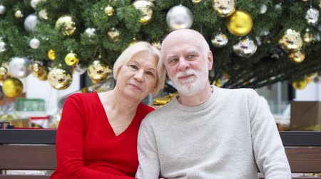 vánoční koule : Portrait of cheerful senior couple near decorated Christmas tree at mall. Happy family sitting and smiling. New Year celebration