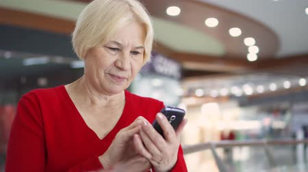 mensageiro : Senior woman standing in shopping mall smiling. Using her smartphone. Modern retired female browsing, reading news, chatting with friends and family. Shopping consumerism concept Stock Footage