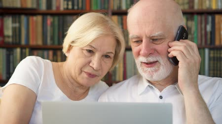 bookkeeping : Senior couple in white t-shirts at home with laptop and smartphone. Family of retired pensioners using cellphone discussing something on screen. Remote freelance work. Home-office concept Stock Footage