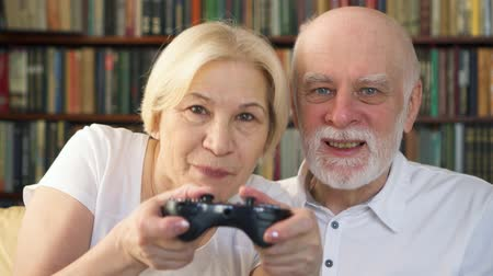 gameplay : Senior couple gamers playing video games at home. Addicted senior players with remote controller of game console. Cybersport for active modern elderly people