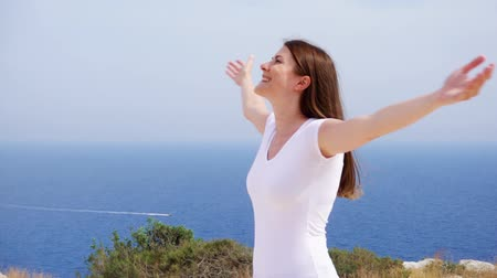 uzanmış : Smiling young woman in white t-shirt spining at cliff against breathtaking view of blue sea. Carefree female raising arms up and dancing in slow motion. Happy overjoyed girl whirling around herself Stok Video