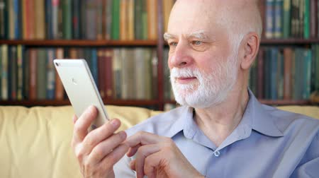 ebook : Handsome elderly senior man relaxing at home reading news on tablet. University professor enjoying retirement reading ebook. Bookcase bookshelves in the background