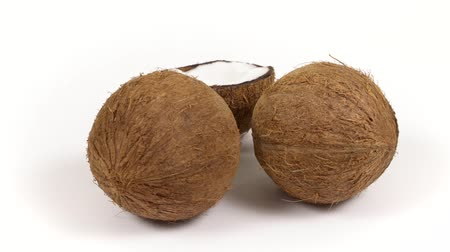 rehydration : Two whole ripe brown tropical coconuts and a half with yummy white pulp rotating on white isolated background. Healthy fresh tropical fruits. Loopable seamless cocos rotating