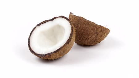 rehydration : Two ripe tropical coconut halves with yummy white pulp rotating on white isolated background. Healthy fresh tropical fruits. Loopable seamless cocos rotating Stock Footage