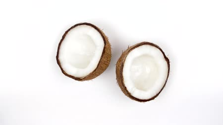 rehydration : Top view of two ripe tropical coconut halves with yummy white pulp rotating on white isolated background. Healthy fresh tropical fruits. Loopable seamless cocos rotating Stock Footage