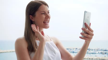 mensageiro : Smiling young woman in white dress using mobile on balcony. Female on vacation enjoying sea view from terrace in morning and having video chat with friend via cellphone messenger app in slow motion Stock Footage