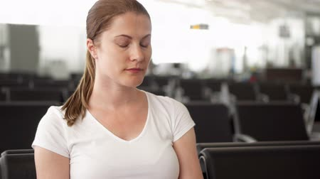 utas : Young woman in white t-shirt sitting in airport waiting room. Female traveler checking time on smart watch while waiting for flight departure. Passenger late for boarding time and run towards gate