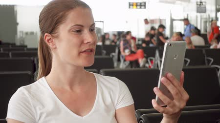 časová prodleva : Woman in white t-shirt sitting in airport waiting room waiting for flight departure. Casual businesswoman talking via messenger app on smartphone. Female traveler smiling waving hand in greeting while