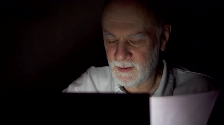 документация : Tired overworked businessman at home working on laptop with documents late at night. Checking data for annual financial report. Secretly using computer hiding from people. Dark only face illuminated Стоковые видеозаписи