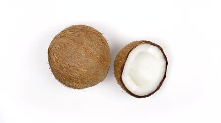 rehydration : Top view of one whole ripe brown tropical coconut and a half with yummy white pulp rotating on white isolated background. Healthy fresh tropical fruits. Loopable seamless cocos rotating Stock Footage