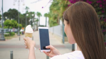 make photo : Young woman in white t-shirt taking photo of ice cream cone outdoors in summer. Happy female teenager photographing vanilla ice cream on her camera phone on street in slow motion